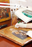 Restorer works on ancient golden icon Royalty Free Stock Photos