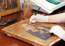 Restorer works on ancient icon Stock Photo