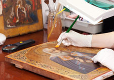 Restorer works on old gilded icon with brush Royalty Free Stock Photo