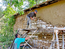 Restoring a house in a traditional manner. Two men restoring an old village house in a traditional manner.The house was built using natural materials, such as Royalty Free Stock Photography
