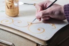 Restoring an old furniture. Handpainting an old furniture decoration with a brush Royalty Free Stock Photo