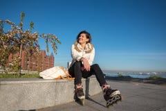 Restos alegres de la muchacha después del patinaje sobre ruedas Foto de archivo libre de regalías