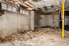 Restos de abandonado interior dañado y destruido de la casa por la granada que descasca con el tejado y la pared derrumbados en e imagenes de archivo