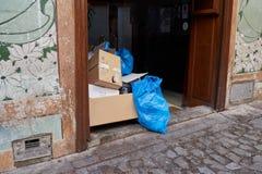 Restos de la basura y basura, las bolsas de plástico y cajas de cartón en el portal de una casa en Toledo, España imagen de archivo