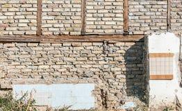 Restos de la casa derrumbada vieja con el tejado quebrado y dañado con la pared de ladrillo del grunge después del desastre fotografía de archivo