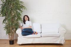 Restos de la muchacha en un diván suave Fotos de archivo