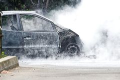 Restos de un coche quemado todavía que arde imagen de archivo