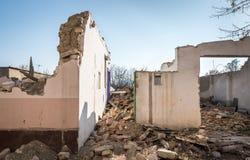 Restos del daño del desastre de las consecuencias del huracán o del terremoto en casas viejas arruinadas con el tejado y la pared imagen de archivo