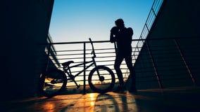 Restos del jinete en un fondo de la puesta del sol Silueta activa del adolescente almacen de metraje de vídeo