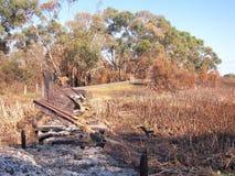 Restos del quemado abajo del puente del pie después de fuego del arbusto Imágenes de archivo libres de regalías