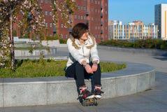 Restos felices de la mujer joven después del patinaje sobre ruedas Foto de archivo libre de regalías