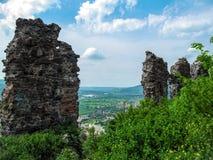 Restos hoscos grises de las paredes de la fortaleza antigua contra la perspectiva del paisaje de la montaña en Khust Ucrania foto de archivo libre de regalías