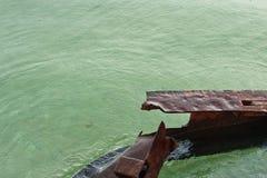 Restos oxidados de un puente en el agua durante la lluvia Imagen de archivo