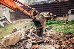 Restos, pedra e concreto hidráulicos da demolição da carga da escavadora do backhoe para reciclar Imagem de Stock