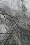 Restos que arden de una casa del ghetto con un agua de rociadura del bombero Foto de archivo libre de regalías