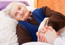 Restos solos mayores de la mujer en la cama Foto de archivo libre de regalías