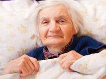 Restos solos mayores de la mujer en la cama Imagen de archivo libre de regalías