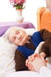 Restos solos mayores de la mujer en la cama Imagenes de archivo