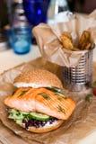 Restourant-Servierteller - Burger mit den Lachsen, Kartoffel auf w braten Lizenzfreie Stockfotografie