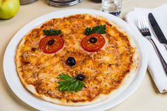 Restourant serving dish for child`s menu  pizza with face Stock Photos