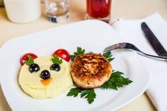 Restourant serving dish for child`s menu  potato puree, cutlet. Restourant serving dish for child`s menu - potato puree, cutlet with face on white background Stock Photo