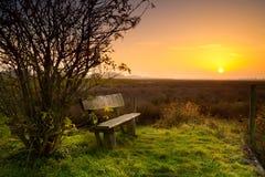 Restplatz mit Bank am Sonnenaufgang Lizenzfreies Stockfoto