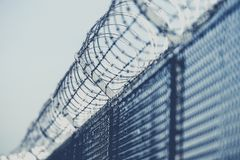 Restricted Area Barbed Fence. Closeup Photo in Bluish Color Grading stock photo