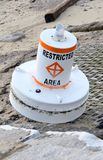 Restricted Area Buoy. A restricted area marking buoy broken from its moorings and washed up on the beach Stock Photo