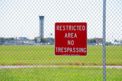 Restricted area no trespassing sign at airport. A RESTRICTED AREA NO TRESPASSING sign on a fence at an airport with the air traffic control tower in the royalty free stock photos