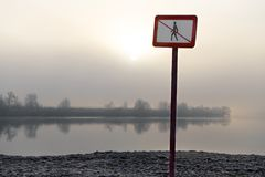 Restricted area sign. On a river bank, a gloomy landscape in the foggy background Stock Photography