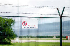 Restricted Area Sign. On Tall Barbed Wire Fence Royalty Free Stock Photo