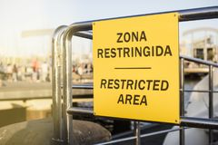 Restricted area signboard, written in Spanish and English.  stock photo