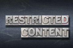 Restricted content den. Restricted content phrase made from metallic letterpress on dark jeans background royalty free stock photography