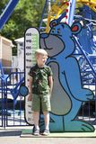 Restrictions on growth in a childrens amusement park. A six year old boy stands against the background of a mans growth line stock images