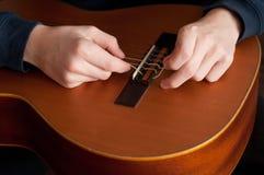 Restring一把古典吉他,关闭 库存图片