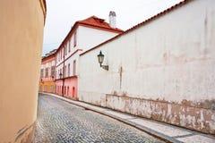 Restringa la via cobbled con le pareti di pietra bianche di vecchia città e delle lanterne Fotografie Stock Libere da Diritti