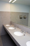 Restroom. A restroom in a department store has tan tiles and three white sinks Stock Photography