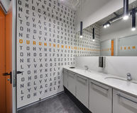 Restroom in a coworking. Ligh colored restroom with black and orange letters on the wall and doors. Doors and walls reflected in the mirror. There are two white Royalty Free Stock Photography