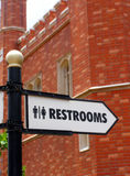 Restroom direction sign. In front of old brick building Stock Image