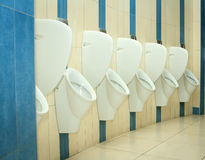 Restroom interior with urinal row Stock Images