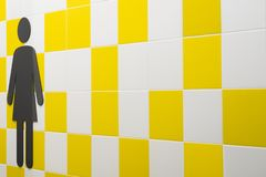 restroom Símbolos das mulheres na parede com quadrados amarelos e brancos Lugar público Copyspace imagens de stock royalty free