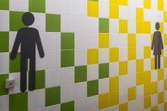 restroom Símbolos de hombres y de mujeres en la pared con los cuadrados coloreados Lugar público Teja amarilla, verde y blanca en foto de archivo libre de regalías