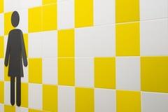 restroom Símbolos de mujeres en la pared con las casillas blancas amarillas y Lugar público Copyspace imágenes de archivo libres de regalías