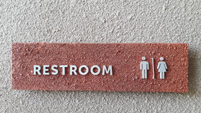 Restroom sign. Is made from red stone which has grey alphabets on in. It is attached with grey wall stock photography