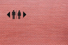 Restroom sign on red brick wall Stock Images