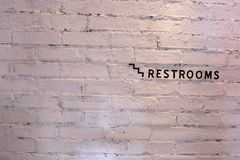 Restroom sign on a white brick wall. The restroom sign sticked on awhite brick wall Stock Photos