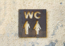 Restroom sign on stone wall. Background closeup Royalty Free Stock Photos