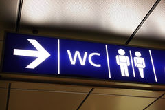 Restroom Signs. Blue backlit restroom panel with arrows and signs Stock Photos