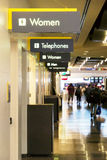 Restrooms in the airport. Restroooms signs in an airport with people royalty free stock photo