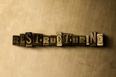 RESTRUCTURING - close-up of grungy vintage typeset word on metal backdrop Stock Photography